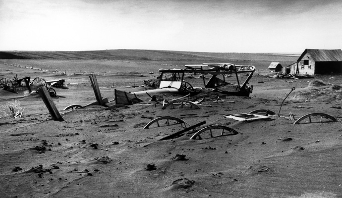 Buried machinery in a barn lot, South Dakota in May 1936. The Dust Bowl on the Great Plains coincided with the Great Depression.