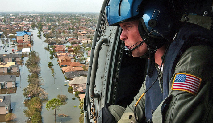 A U.S. Coast Guardsman searches for survivors in New Orleans in the aftermath of Katrina.