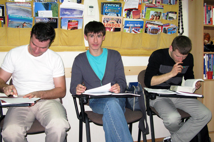 Filling out course evaluation forms at Terra Nova. From left to right: Andrei Buşmachiu, Gleb Miron, Sergiu Opinca. TOEFL Preparation / Section 5 (Sat.Sun. Morning Group). May 2012.