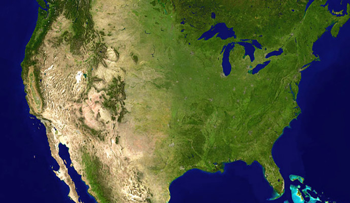 A satellite composite image of the contiguous United States. Deciduous vegetation and grasslands prevail in the east, transitioning to prairies, boreal forests, and the Rockies in the west, and deserts in the southwest. In the northeast, the coasts of the Great Lakes and Atlantic seaboard host much of the country's population.